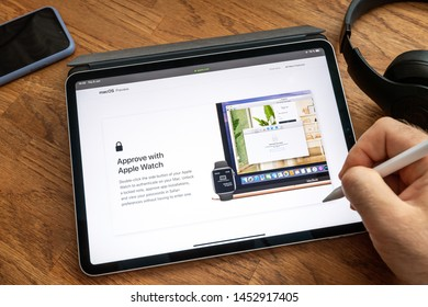 Paris, France - Jun 6, 2019: Man reading on Apple iPad Pro tablet about latest announcement of at Apple Worldwide Developers Conference WWDC - authentication to laptop with watch