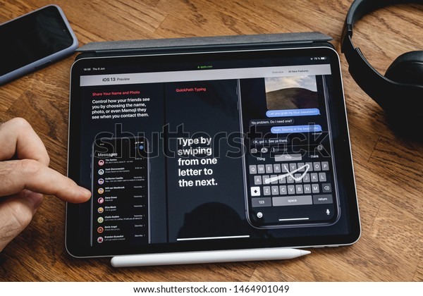 Paris, France - Jun 6, 2019: Man reading on Apple iPad Pro tablet about latest announcement of at Apple Worldwide Developers Conference showing the iOS 13 feature type by swiping