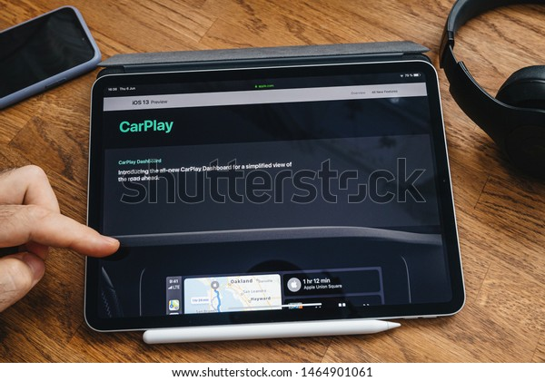 Paris, France - Jun 6, 2019: Man reading on Apple iPad Pro tablet about latest announcement of at Apple Worldwide Developers Conference showing the iOS 13 feature new CarPlay dashboard