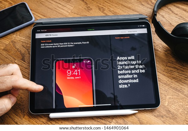 Paris, France - Jun 6, 2019: Man reading on Apple iPad Pro tablet about latest announcement of at Apple Worldwide Developers Conference showing the iOS 13 feature Faster unlock
