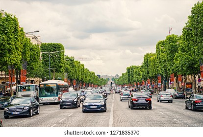 Paris, France - June 02, 2017: avenue Elysian Fields with street traffic and green trees on cloudy sky background. Landmark and sightseeing. Summer vacation and travel concept, triumphal arch road