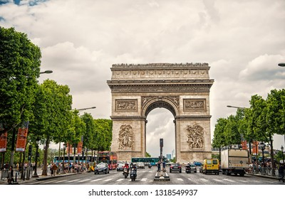 Paris, France - June 02, 2017: Arch monument in centre of busy avenue. Arc de Triomphe on cloudy sky. Vacation and sightseeing in french capital. Victory liberation and honour concept.