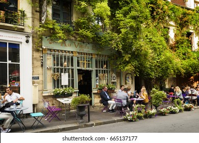 "Paris, France, June 04, 2017 : Style of life in Paris, France bistrrots and people on terraces. Here, this is ""The old Paris"" traditional bistrot in spring time, near Notre dame, Paris, France."