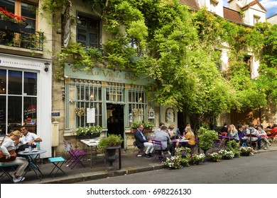 "Paris, France, June 04, 2017 : Famous style of life in France with bistrots. People on terraces. This is ""The old Paris"" traditional bistrot. Ile de la Cite near Notre dame, Paris, France."