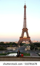 PARIS, FRANCE - JUNE 05, 2008: Asian tourist sitting on a wall in Trocadero, with the view of the Eiffel tower in the background