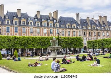 PARIS, FRANCE - JUNE 10, 2015: Paris Place des Vosges. People relaxing on green lawns of famous Place des Vosges - oldest planned square in Marais district. Place des Vosges was built in 1605 - 1612.