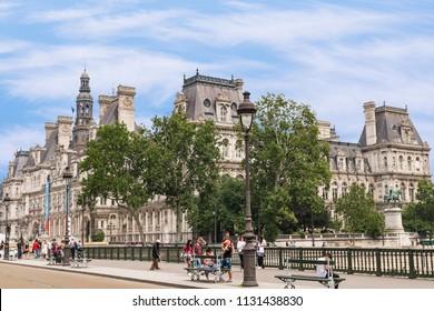 PARIS, FRANCE - June 11, 2018: Paris City Hall building and people walking a bridge across the Seine River.