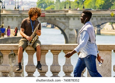 Paris, France - June 13, 2014: Paris street artist plays saxophone on the bannister while other person listens headphone.