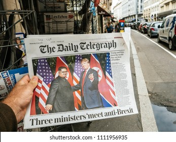 PARIS, FRANCE - JUNE 13, 2018: Man buying The Daily Telegrph newspaper at press kiosk showing on cover U.S. President Donald Trump meeting North Korean leader Kim Jong-un in Singapore