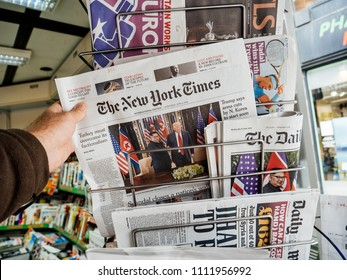 PARIS, FRANCE - JUNE 13, 2018: Man buying The New York Times newspaper at press kiosk showing on cover  U.S. President Donald Trump meeting North Korean leader Kim Jong-un in Singapore