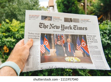 PARIS, FRANCE - JUNE 13, 2018: Man reading The New York Times newspaper  showing on cover  U.S. President Donald Trump meeting North Korean leader Kim Jong-un in Singapore