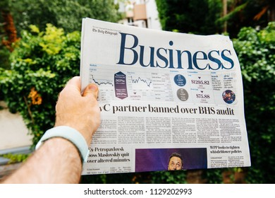 PARIS, FRANCE - JUNE 13, 2018: Man holding newspaper The Daily Telegraph Business section with PwC partner banned over BHS audit