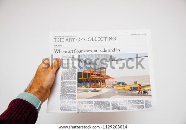 PARIS, FRANCE - JUNE 13, 2018: Man holding newspaper The New York Times newspaper about Art Basel Modern art exhibition in Basel, Switzerland