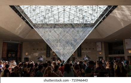 PARIS, FRANCE - JUNE 17, 2017: Inside the inverted pyramid at the Louvre Museum in Paris. Busy crowds of people in the Carrousel du Louvre.