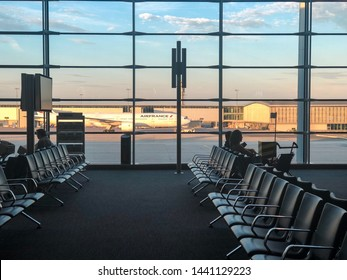 Paris / France: June 17 2019: Passengers are waiting for their flight at the gate in Terminal E while Air France Boeing jet is taxiing in the background