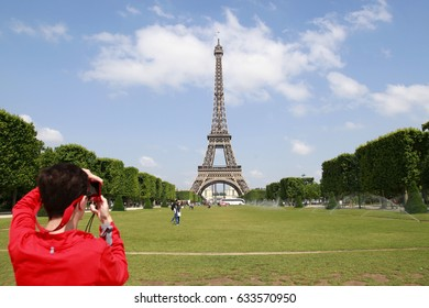 PARIS, FRANCE - JUNE 18 2014: Tourist taking photos in front of the Eiffel Tower, the most famous symbol of Paris, June 18, 2014