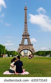 PARIS, FRANCE - JUNE 18 2014: Romantic couple in front of the Eiffel Tower, the most famous symbol of Paris, June 18, 2014