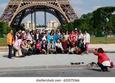 PARIS, FRANCE - JUNE 18 2014: A large number of tourists taking photos in front of the Eiffel Tower, the most famous symbol of Paris, June 18, 2014