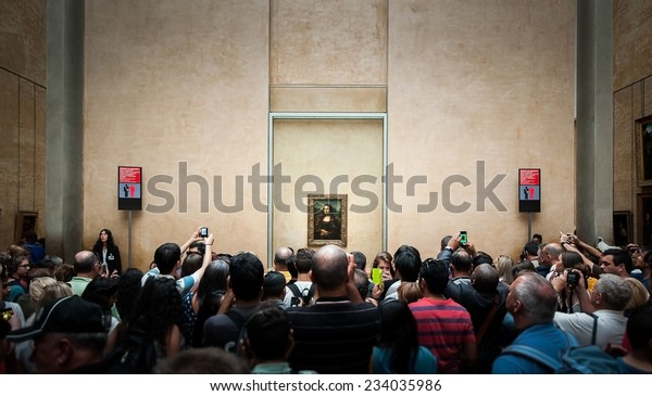 """PARIS, FRANCE - JUNE 18 , 2014 : A many of visitors take photos of """"Mona Lisa"""" , by Leonardo DaVinci's  at the Louvre Museum, june 18, 2014 in Paris, France."""