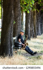 Paris, France - June 18, 2017: Street musician plays the saxophone outdoor on the embankment of the river Seine