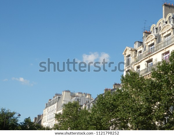 paris, france - june 18 2018 : facade of old buildings lighted by evening sun, tree foliage in the foreground
