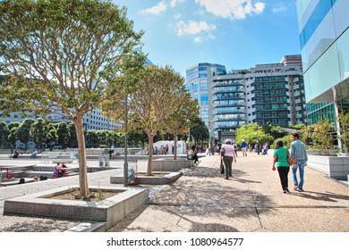 Paris, France - June 19, 2015: La Defense - modern business and financial district in Paris with highrise buildings. Green recreation area. People walking down the street