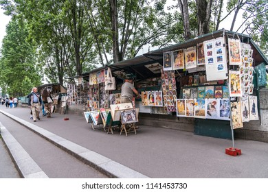 "Paris, France - June 19, 2018: ""Bouquiniste"" bookstalls along River Seine are a favorite Left Bank writers' retreat and source for used books.  This tradition started in the 16th Century."