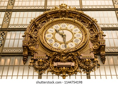 Paris, France - June 19, 2018: Old railway station golden clock and wall of glass in Musée d'Orsay, Museum d'Orsay, in Paris.
