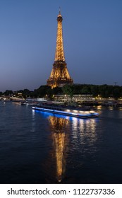 PARIS, FRANCE - June 20, 2018: Eiffel Tower lights at night reflecting in the River Seine in Paris France.
