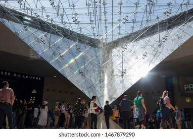 Paris, France, June 20, 2018: Sun coming through glass pyramid by Louvre entrance