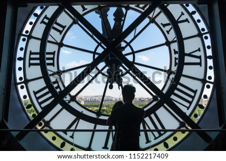 PARIS, FRANCE - June 20, 2018: Man and child looking at Paris cityscape, skyline view through the clock face at the Musée d'Orsay.