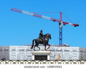 Paris, France - June, 2018:  Equestrian statue of Henry IV. Place du Pont Neuf. Quai du Louvre. Banner on the facade of the building under repair, construction crane, blue sky