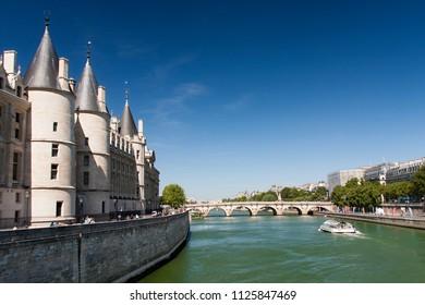 Paris, France, June 2018: Wide angle view of la conciergerie palace and seine river in paris, as seen from pont au change bridge