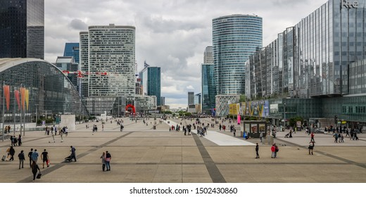 Paris, France - June 2019 : Businessmen and people who walk and go to work on the forecourt of la Defense the largest business center in europe in Paris France