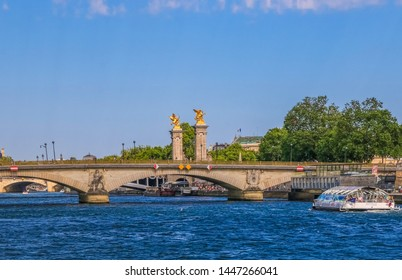 Paris, France - JUNE 2019: Great panoramic view of the Pont des Invalides. The Batobus, a river-boat shuttle service, is moving towards the lowest bridge traversing the Seine in Paris.