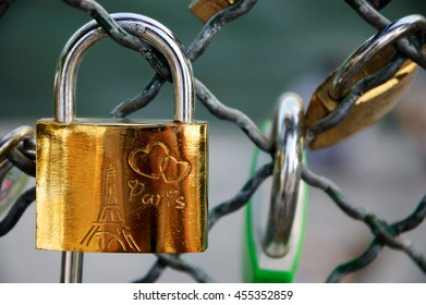 PARIS, FRANCE - JUNE 21, 2014: Love lock with Eiffel tower and hearts carving attached to bridge. Ritual of affixing padlocks, as symbol of love, to bridge's fence is spread in Europe from 2000s.
