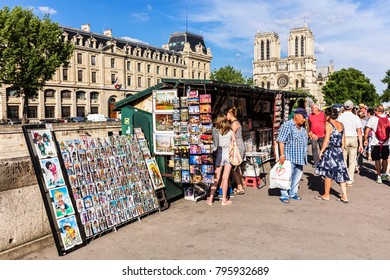 Paris, France - June 23, 2017: Vintage books and paintings in open bookmarket on embankment of River Seine near Notre Dame de Paris Cathedral. The bookmarket is there since the 16th century.