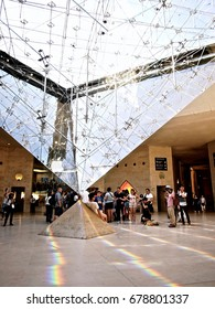 PARIS, FRANCE - JUNE 24, 2014: Tourists are gathering around La Pyramide Inversee or The Inverted Pyramid, a famous landmark inside the Carrousel Du Lourve shopping mall.