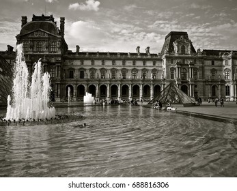 PARIS, FRANCE - JUNE 24, 2014: Part of Louvre museum and the fountain pond in black and white during the bright sunny day.