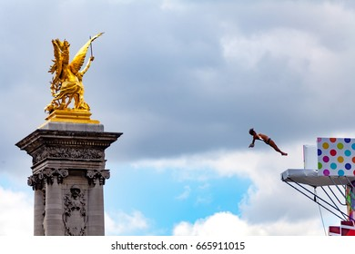 Paris, France - June 24, 2017 :  Diving athlete demonstrating over the Seine river during the Paris Olympic Games 2024 showcase.
