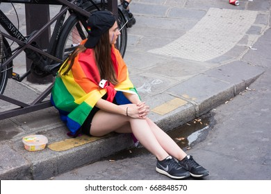 PARIS, FRANCE - JUNE 24, 2017:  Girl sits on the ground with pride cape at the Gay Pride.