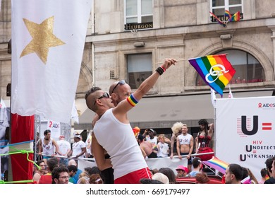 PARIS, FRANCE - JUNE 24, 2017: Men on float parade above the crowd at the Gay Pride parade.