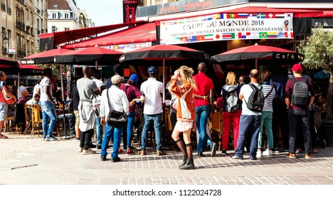 PARIS, FRANCE - JUNE 24, 2018: People watching 2018 football world cup games (Senegal and Japan teams playing) at Parisian cafe bar terrace.