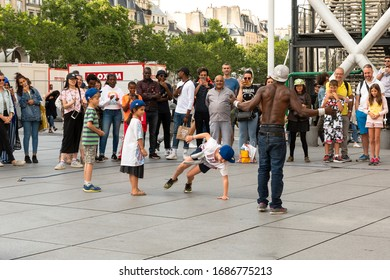 PARIS, FRANCE - JUNE 24, 2018: Parisian urban scene. Multicultural people, locals and tourists, watch entertainer dancing with kids invited from public. Dozens street artists perform everyday in Paris