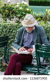 Paris, France - June 25, 2017: Senior elegant man in a hat siting on a chair outside in the inner courtyard of the Royal Palace (Palais-Royal) and reading a book.