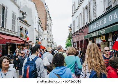 PARIS, FRANCE - JUNE 26, 2016: Crowd of people walk the street in Monmartre quarter. Paris is the mos visited city in the world.