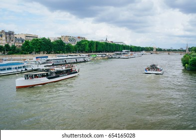 PARIS, FRANCE - JUNE 26, 2016: Tourist city tour cruise ships on Seine river on cloudy summer day. Paris is the most visited city in the world.