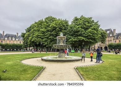 PARIS, FRANCE - JUNE 26, 2017: People on green lawns of famous Place des Vosges. Place des Vosges - oldest planned square (1612) in Paris, in Marais district.