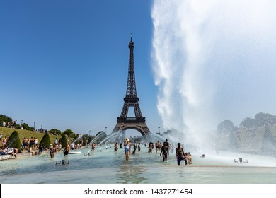 Paris, France, June 27, 2019: tourists and locals taking a bath in the Jardins du Trocad ro Guardians of the Trocadero under the powerful water cannons. new heat records over 45 degrees celius