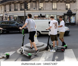Paris, FRANCE - June 27, 2019: people with Lime electric scooters, rented through a mobile app and dropped off anywhere in the French capital near the Notre Dam